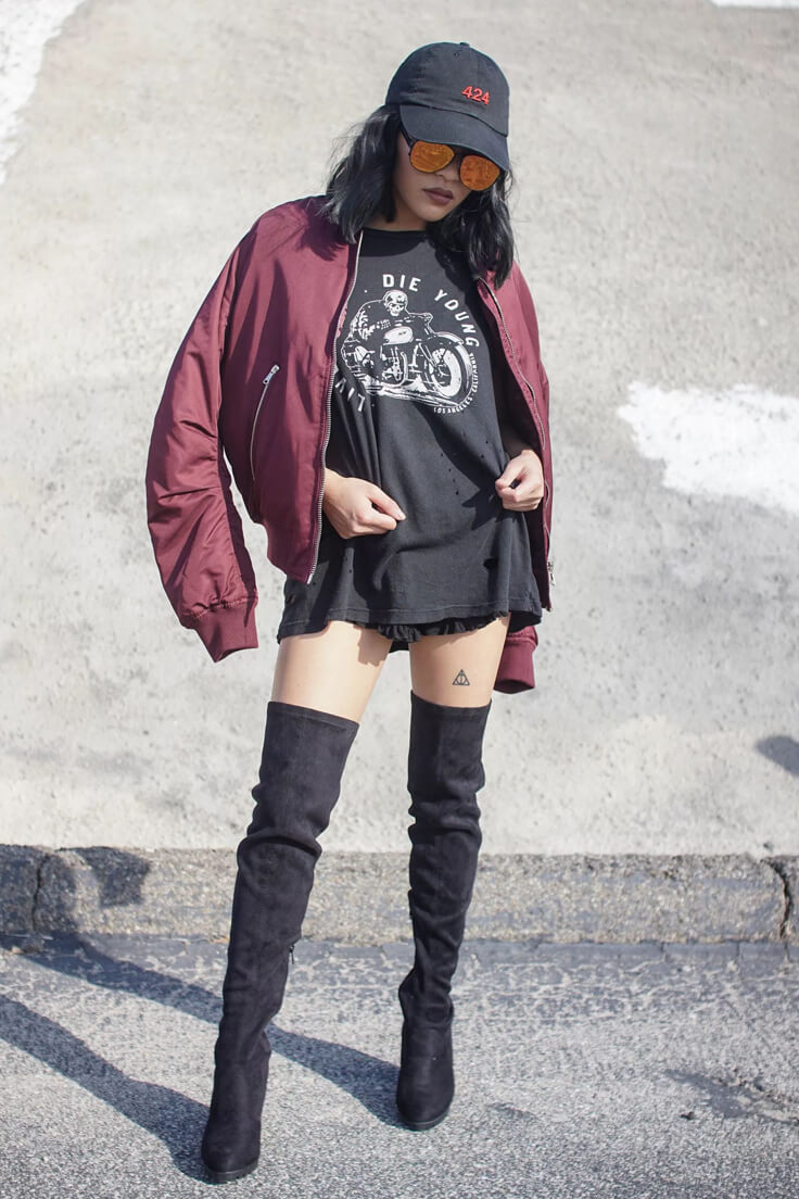 Woman in burgundy bomber jacket, oversized black t-shirt, оverknees boots, black cap