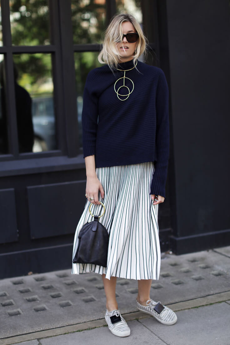 relaxed and comfortable outfit for spring: dark blue ribbed wool turtleneck sweater, pleated stretch-knit skirt, plaque-detailed striped sneakers