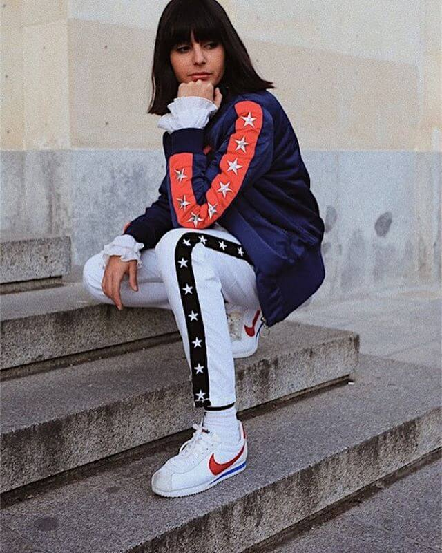 Fashion stylist Maria Bernad is wearing a satin hip-hop style bomber jacket, white track pants, and Nike classic Cortez leather
