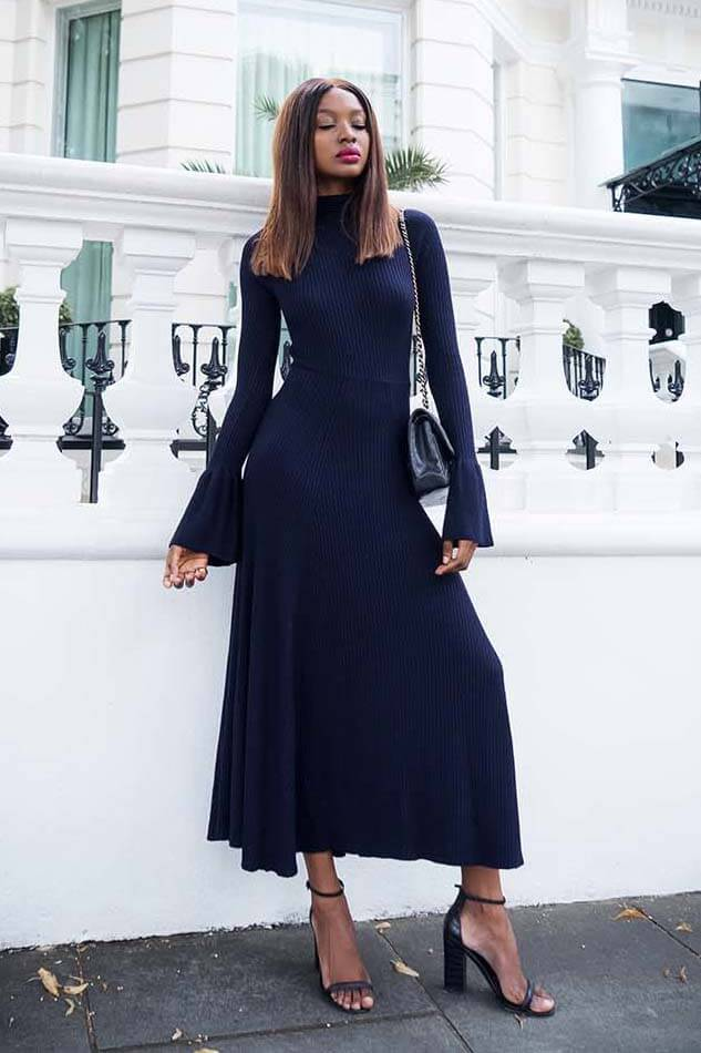 Outfit details — ribbed dark blue maxi dress with flounces paired with black heeled sandals. A woman looks totally feminine by putting on just knitted maxi dress and sandals.