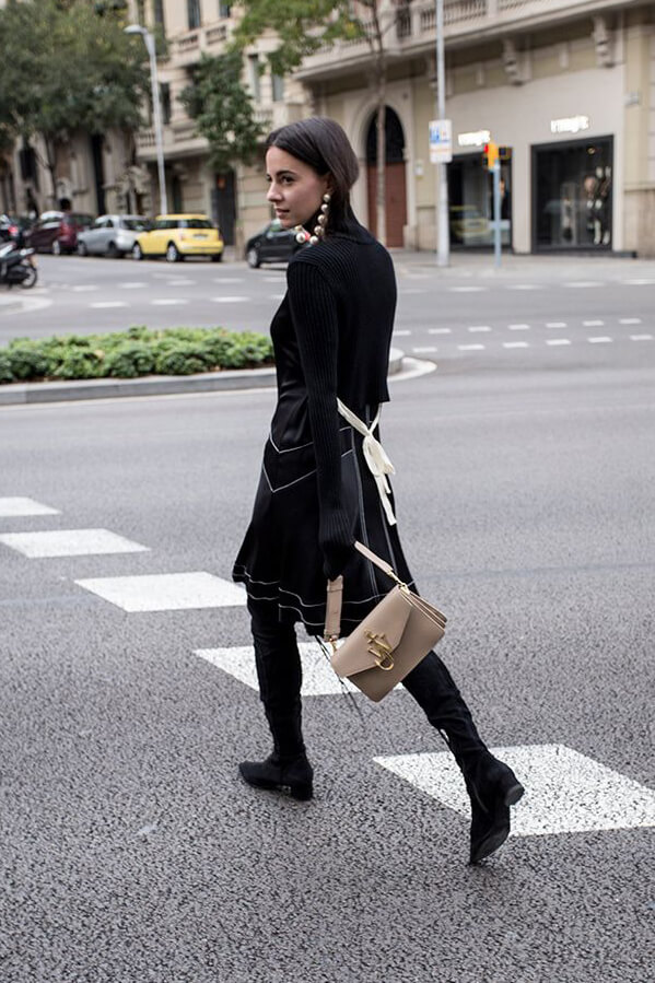 Zina Charkoplia demonstrates the combination of the black silk dress with knitted sleeves and black suede overknee boots adding a nude color bag and pearl drop earrings