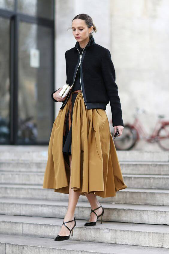 Street Style star goes for a wool-blend bomber jacket with A-line midi skirt and black pumps with crisscrossing straps