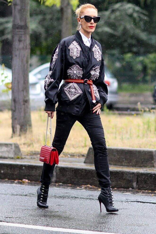 Woman is wearing belted bomber jacket with patches, black leather ankle boots, and red bag