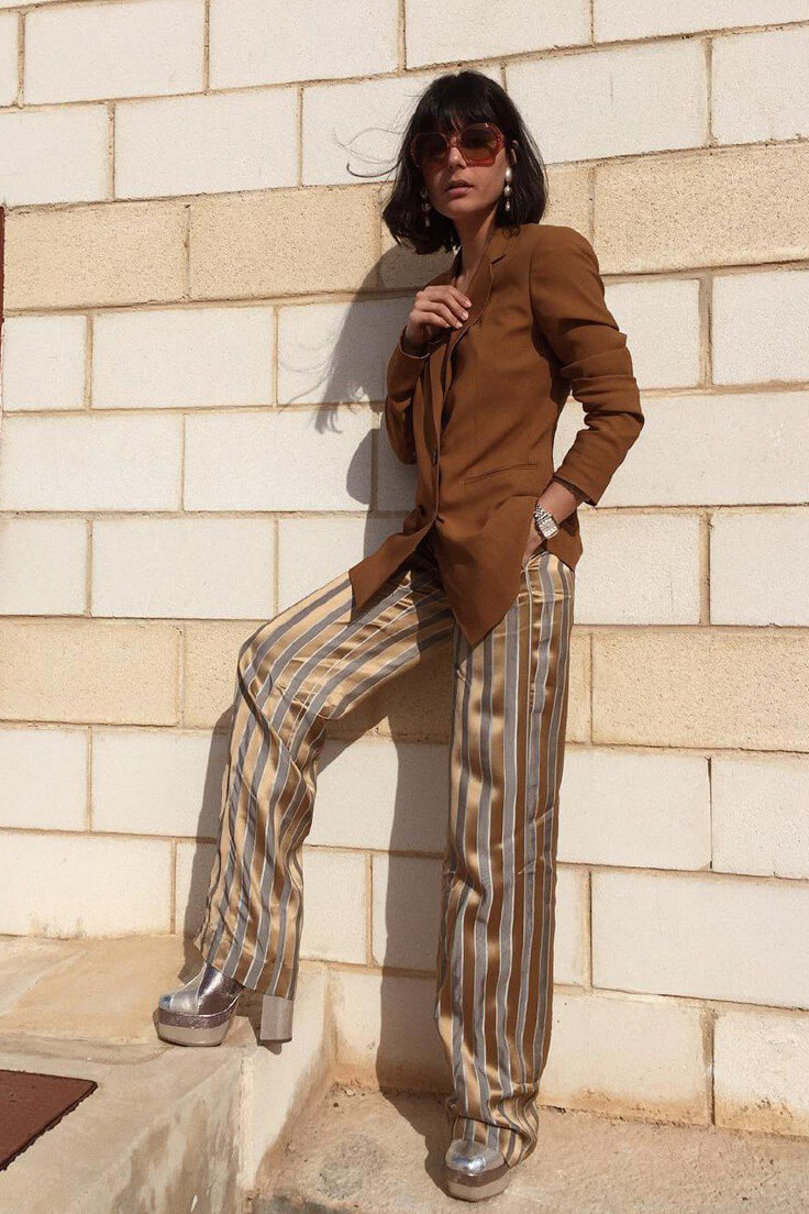 Wearing brown blazer, silk striped wide-leg pants with silver platform boots