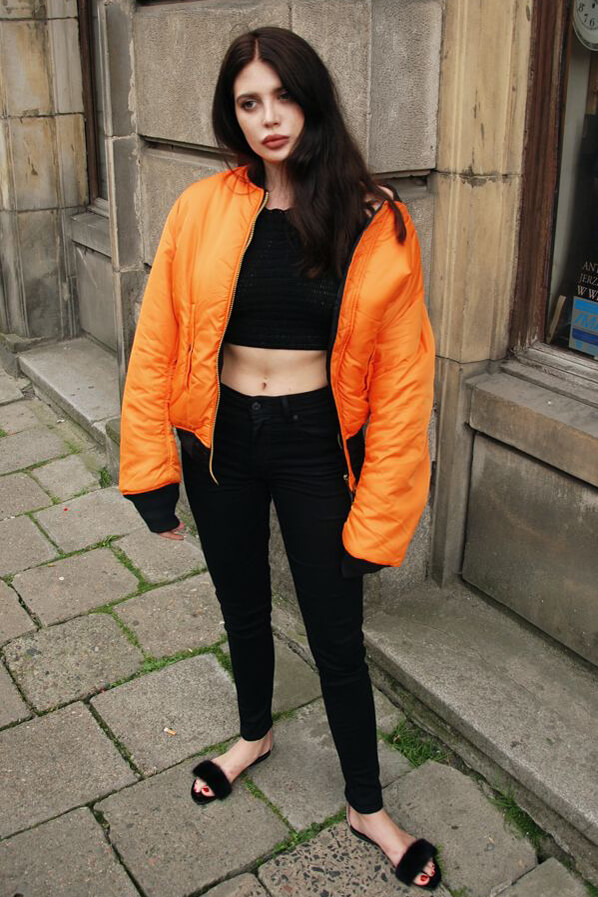 An extravagant look: woman wearing crochet bikini top, Levi's High Rise Skinny jeans, Alpha Industries MA-1 jacket, faux fur sandals