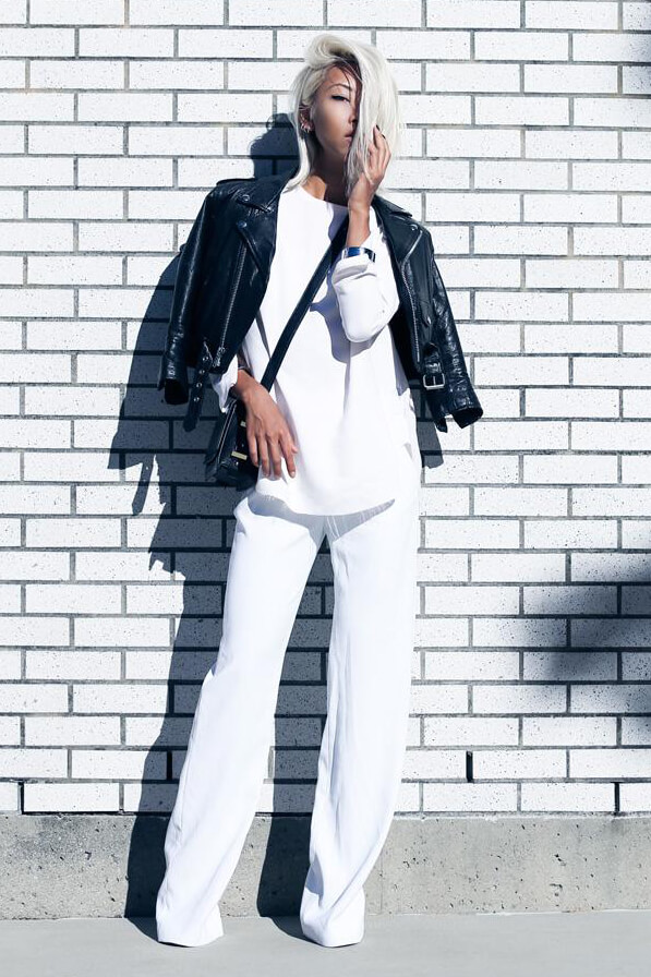 The fashion blogger is wearing white wide leg pants, white blouse, and black cropped leather jacket