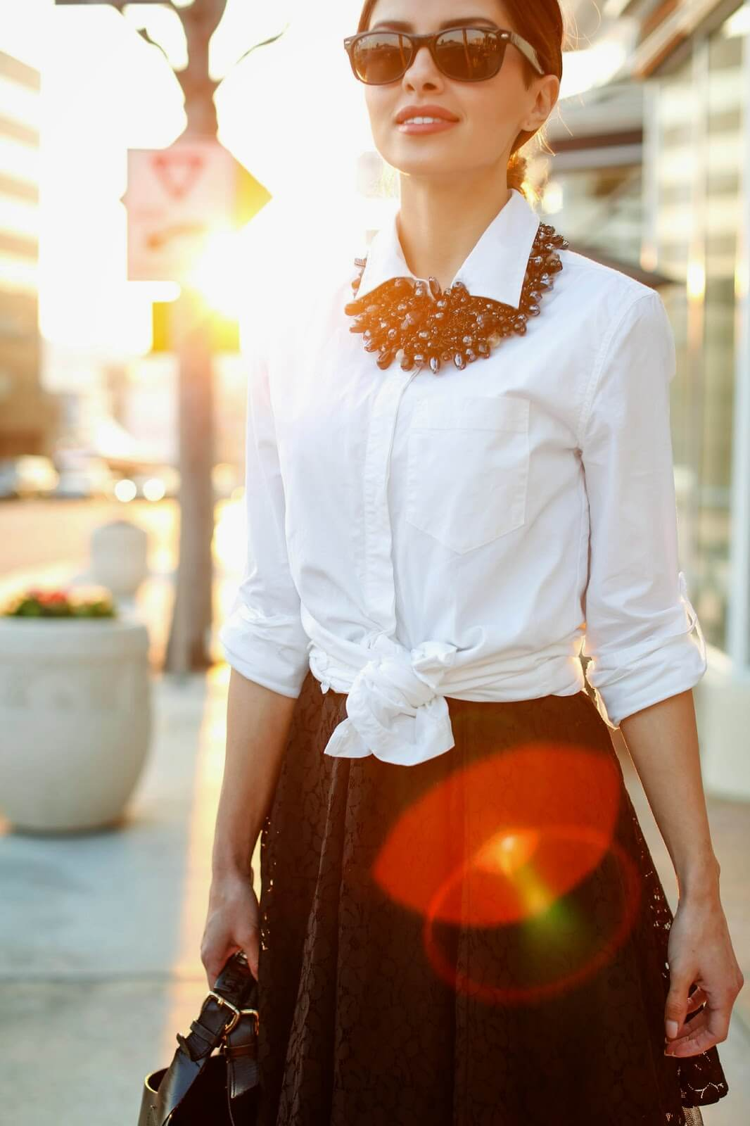 Smiling woman wearing a white shirt with a bow on the chest and massive black necklace made of shiny pendants