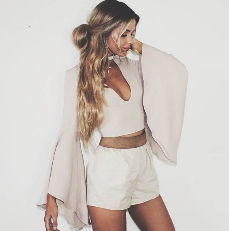 Stylish blonde is wearing a dusty pink bell sleeve top and beige shorts. Bring out your romantic side in an outfit of loose beige shorts and a cropped bell sleeve top.