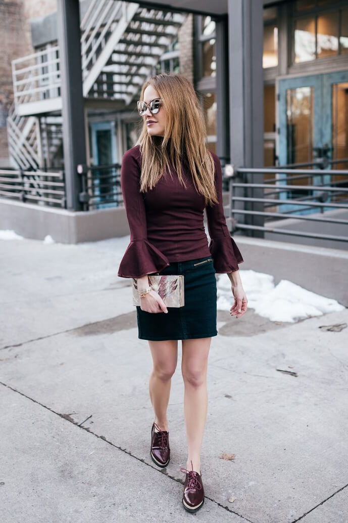 Stylish blonde is wearing a burgundy bell sleeve top and a dark denim mini skirt. Anything goes when it comes to bell sleeves, even deep burgundy matched with dark denim.