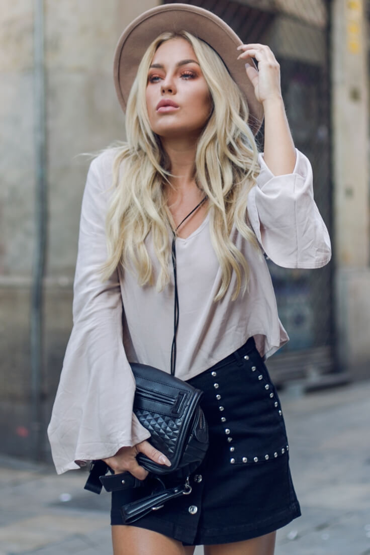 Trendy blonde is wearing a pale pink bell sleeve top and combat boots. Stay warm and comfortable in an oversized bell sleeve top on an overcast day.