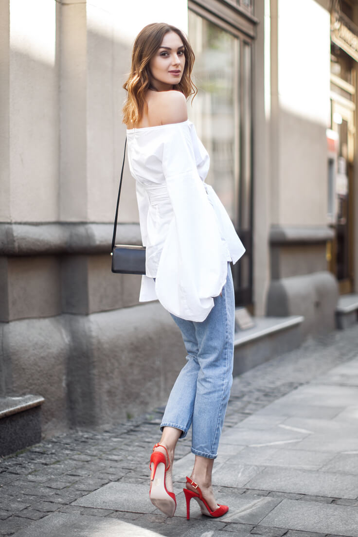Trendy blonde is wearing blue boyfriend jeans and a white off-the-shoulder bell sleeve blouse. Get the look by pairing blue boyfriend jeans and red statement heels with a bell sleeve off-the-shoulder blouse in stark white cotton.