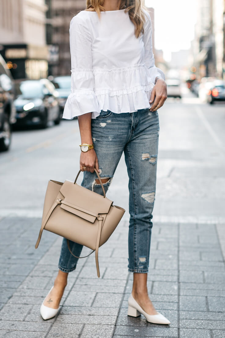 Stylish blonde wearing ripped boyfriend jeans and a peplum bell sleeve top. Bell sleeves, peplum plus boyfriend jeans make an unexpected winning combination.