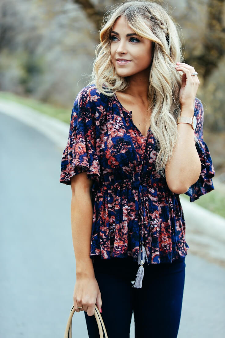 Trendy blonde wearing dark blue skinny jeans and a V-neck floral blouse. Match dark denim and girly florals to create this season's trendiest look.