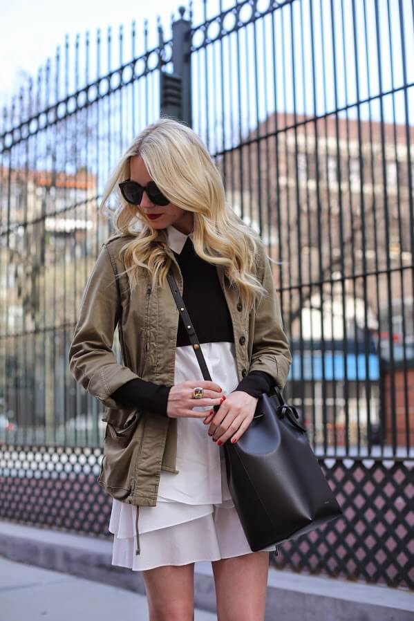 Fashionista wearing white shirt dress with chiffon ruffle finish and military jacket.