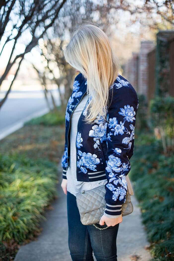 Trendy blonde woman in denim jeans and a blue floral bomber jacket. A floral bomber jacket is an urban twist to spring's flowery trend.