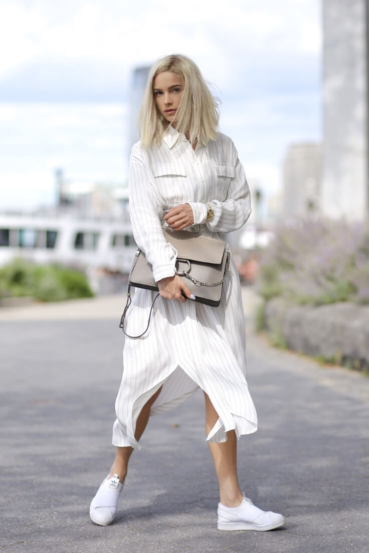 Blondie with midi length linen shirt dress and white sneakers representing cozy-glam look.
