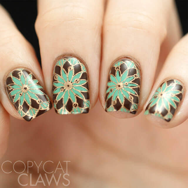 This boho nail design from Copycat Claws incorporates an earthy teal, brown, and gold color scheme. The gold floral pattern has been stamped on over a brown base, and the petals have been filled in with a mint green polish.