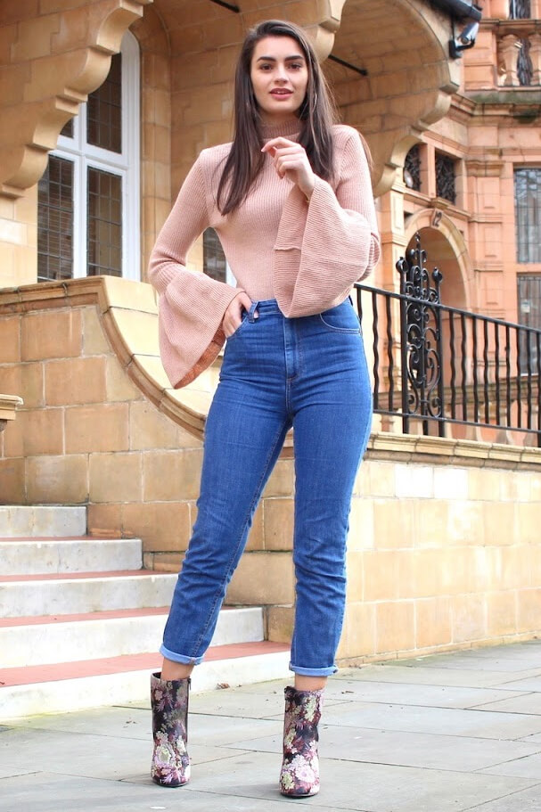 Fashionable brunette is wearing high-waisted jeans and a blush pink woolen bell sleeve sweater. Ease yourself into spring in a turtleneck bell sleeve sweater and trendy high-waisted mom jeans.