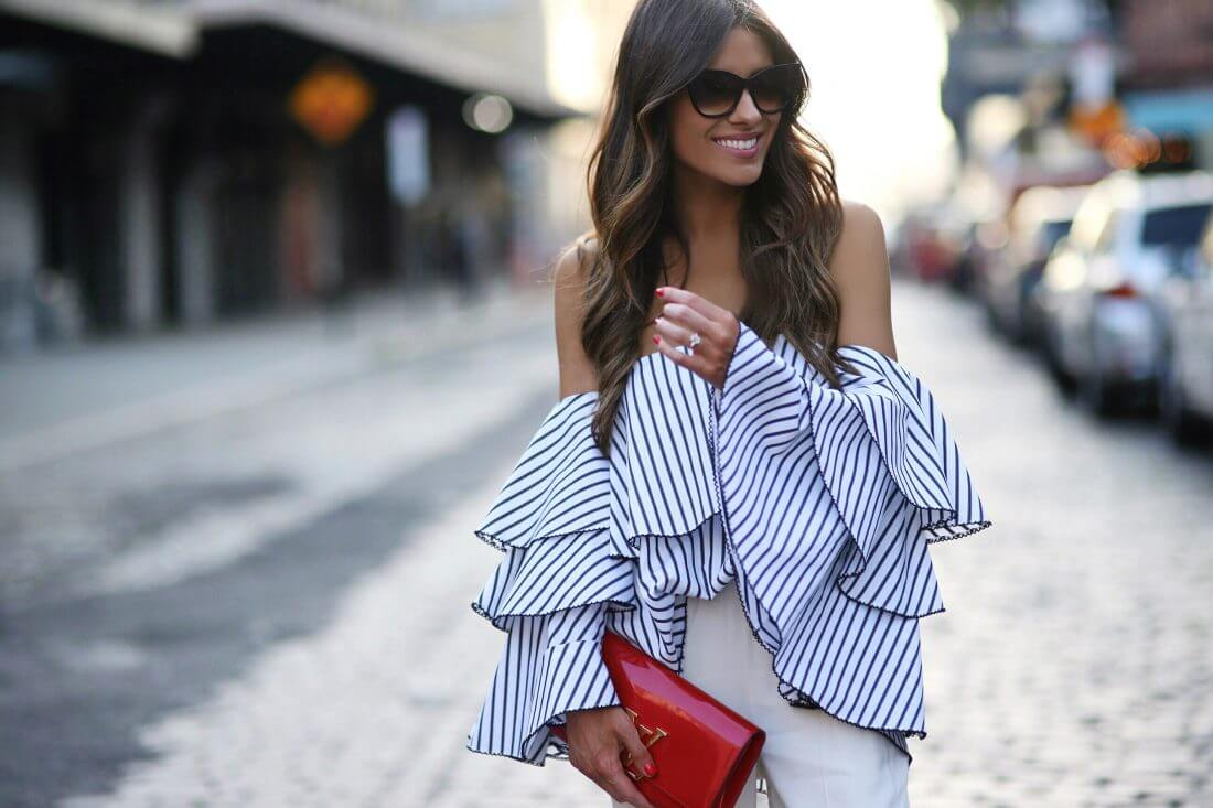 Stylish brunette in striped off-the-shoulder bell sleeve top and white pants. Get in on the striped trend by choosing an off-the-shoulder top complete with billowing bell sleeves.