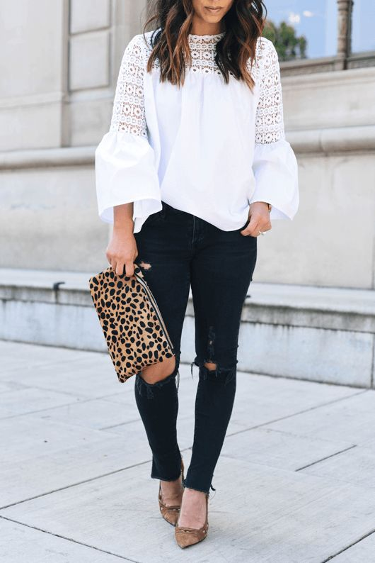 Chic brunette is wearing ripped denim jeans and a white lace bell sleeve blouse. A pure white bell sleeve top creates a stark contrast against skinny black jeans.