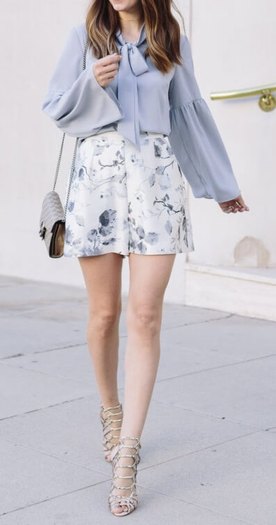 Elegant brunette is wearing a lilac bell sleeve blouse and floral shorts. Look like a French style icon in a springtime ensemble of floral shorts and violet bell sleeves.