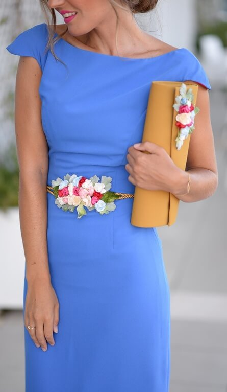 Chic brunette wearing a fitted blue dress and a floral belt. All it takes to brighten up a plain blue dress is a lovely floral belt tied around the waist.