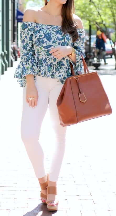 Elegant brunette wearing white skinny jeans and a floral off-the-shoulder bell sleeve blouse. Springtime means bright flowers in the shape of a patterned bell sleeve blouse matched with white denim.