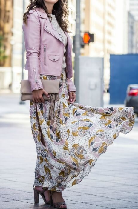 Trendy brunette wearing a floral maxi skirt and a pale pink leather jacket. Let your creative side loose and blend decadent pastel fabrics with a pretty floral maxi skirt.