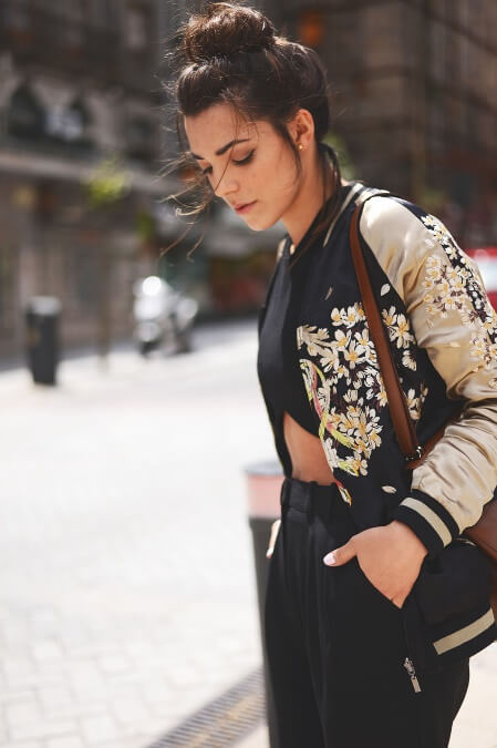 Trendy brunette is wearing black pants and a light floral jacket. Get edgy, modern street style by pairing loose black pants with a sweetly feminine light floral jacket.