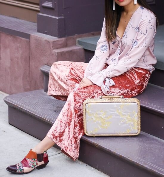 Stylish brunette is wearing pink velvet pants and a floral blouse. Get with the fashion crowd and match pink velvet with pale pink florals.