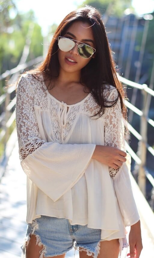 5795c605ca0b3c Trendy brunette wearing denim cut-off shorts and a prairie-style lace bell  sleeve