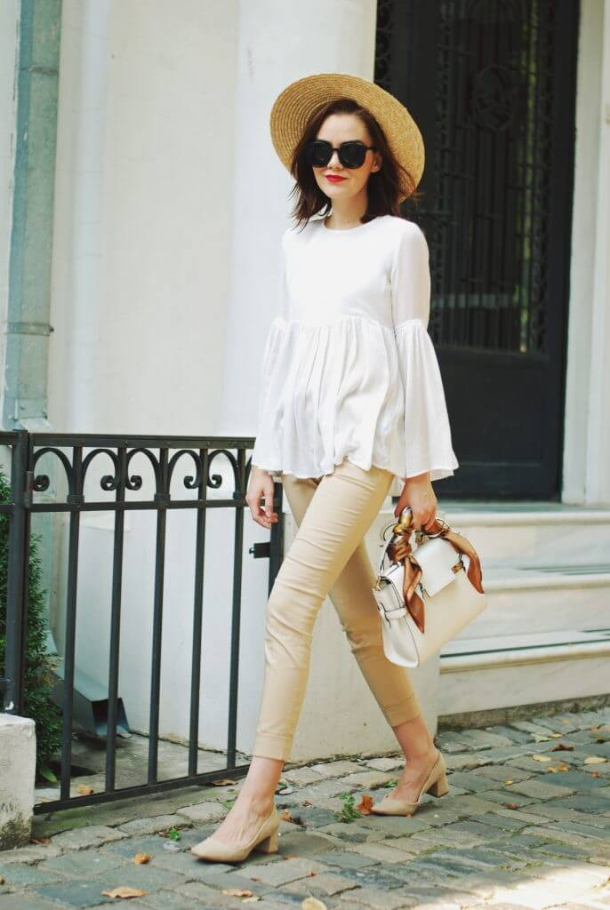 Chic brunette is wearing skinny camel pants and a white bell sleeve blouse. Channel your inner Audrey Hepburn in this classic mix of camel pants and a white bell sleeve blouse.
