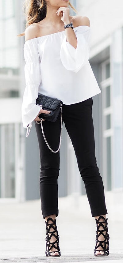Elegant brunette is wearing skinny black pants and a white off-the-shoulder bell sleeve blouse. Yes, monochrome can be sexy – just pair an off-the-shoulder bell sleeve blouse with strappy statement heels.
