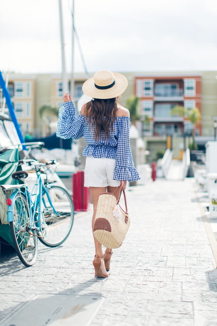 Chic brunette is wearing white shorts and a gingham-print off-the-shoulder blouse with bell sleeves. Pull out those white shorts for sleek spring style, matched effortlessly with a gingham-print bell sleeve blouse.