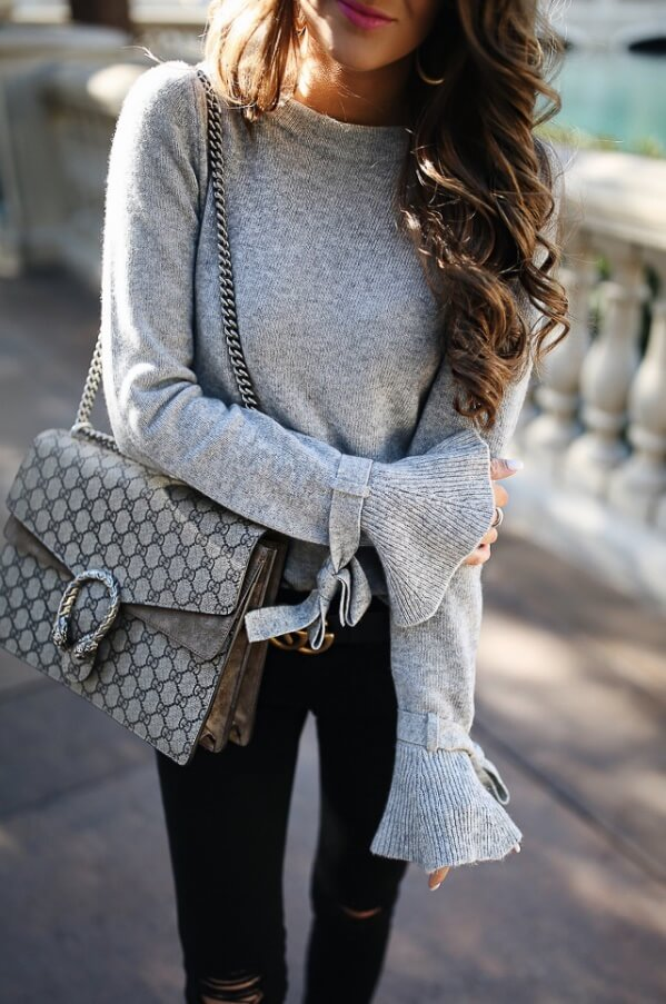 e57cb12b657d4 Trendy brunette wearing black ripped skinny jeans and a woolen bell sleeve  top. Stay stylish