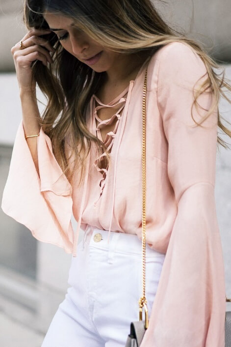 Chic woman in a blush pink lace-up bell sleeve top and white high-waisted pants. Live out your feminine fantasies in this beautiful blend of blush bell sleeves and crisp white linen.