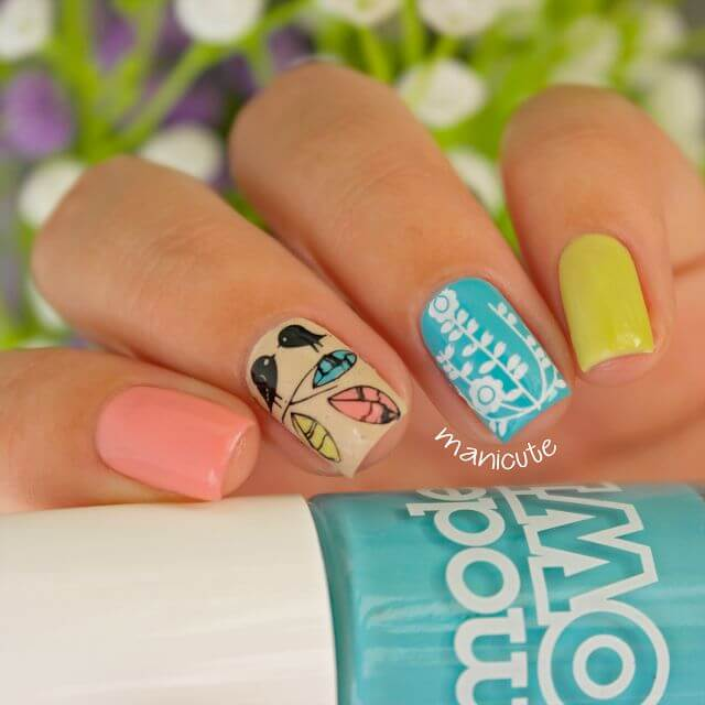 Create a different story on each nail with this unbelievably cute decorative manicure. Between opaque washes of pastel pink and yellow on the pointer and pinky finger, there is a bird and flower patterns on the beige and teal nails respectively, created using the stamping technique.