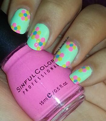 This is a design even beginners can tackle. Using the opposite end of a paint brush dot pink, blue, and yellow in the shape of a flower over a vibrant mint green base.
