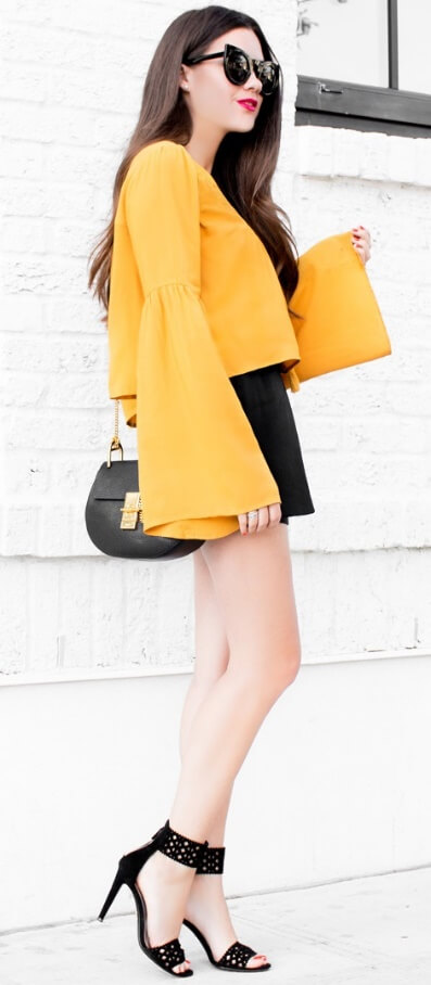 Elegant brunette is dressed in a yellow bell sleeve blouse and black high-waisted shorts. To stand out in a crowd, choose one statement piece to define your outfit like this bold bell sleeve blouse in bright yellow.