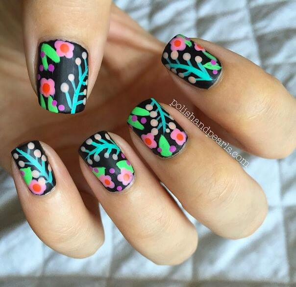 For a tropical effect, try using a black background on your floral nail art. The contrast between the dark background and the light blue, green, and pink flowers creates an almost neon effect.