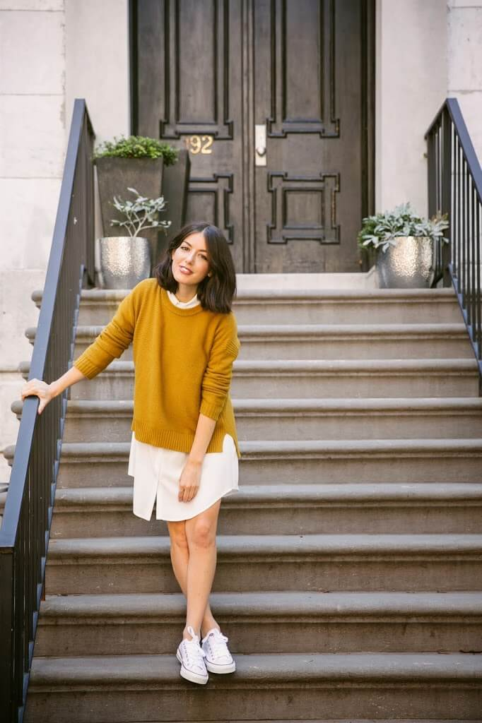 A girl dressed in a white shirtdress and mustard sweater