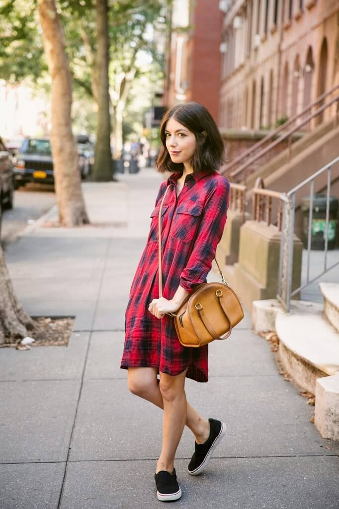Casually dressed girl in a checked print shirt dress and black sneakers