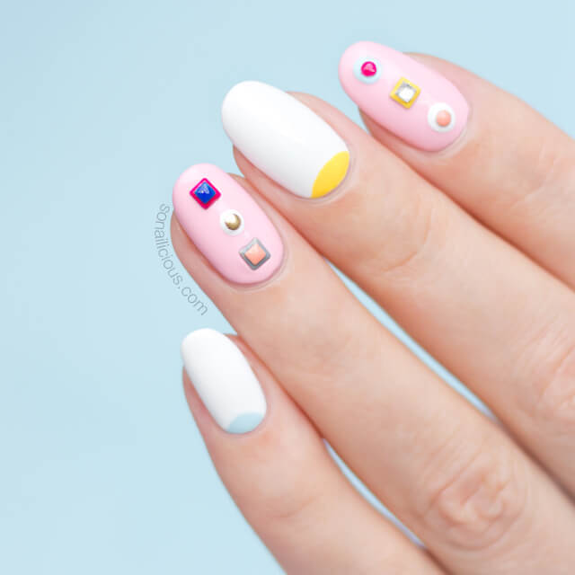 Nothing says spring more than pastel pinks, blues, and yellows. Incorporate this spring color scheme into your look with trendy geometric shapes like these blue and yellow half-moons over a white matte base. On alternating nails, glue or stamp multi-colored studs over a matte pastel pink base.
