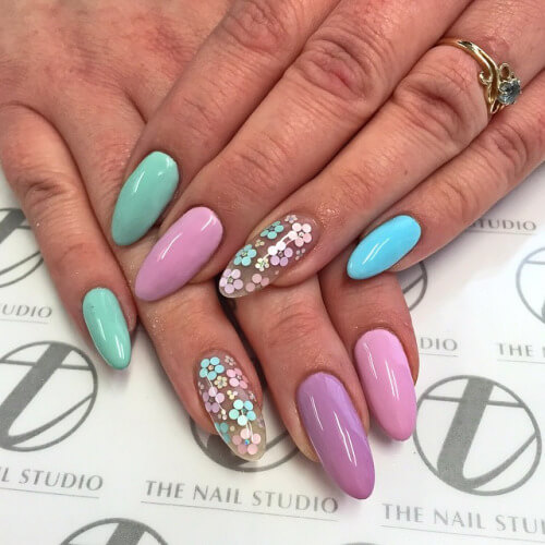 These opaque pastel nails reminiscent of Easter eggs are accented by an attractive floral pattern over a clear gel nail base.