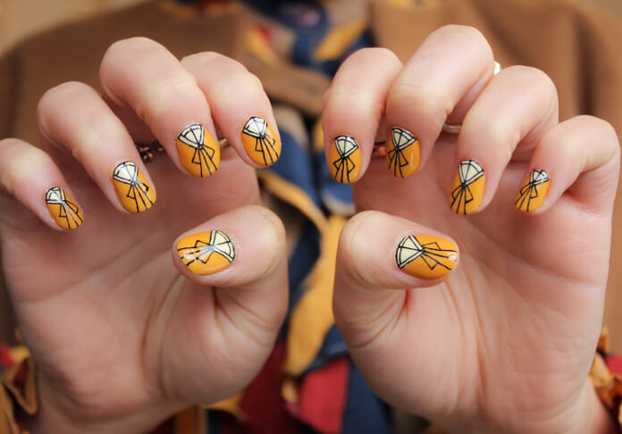 One-of-a-kind orange, white, and black nail art that will have your friends oohing and ahhing over your nails. This nail art is inspired by the symmetrical, triangular designs of the Art Deco period