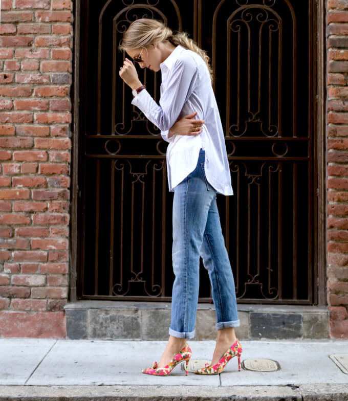 Stylish blonde in blue cuffed jeans and floral stiletto heels. Blue denim and a button-down shirt get a floral upgrade with sunny floral pumps.