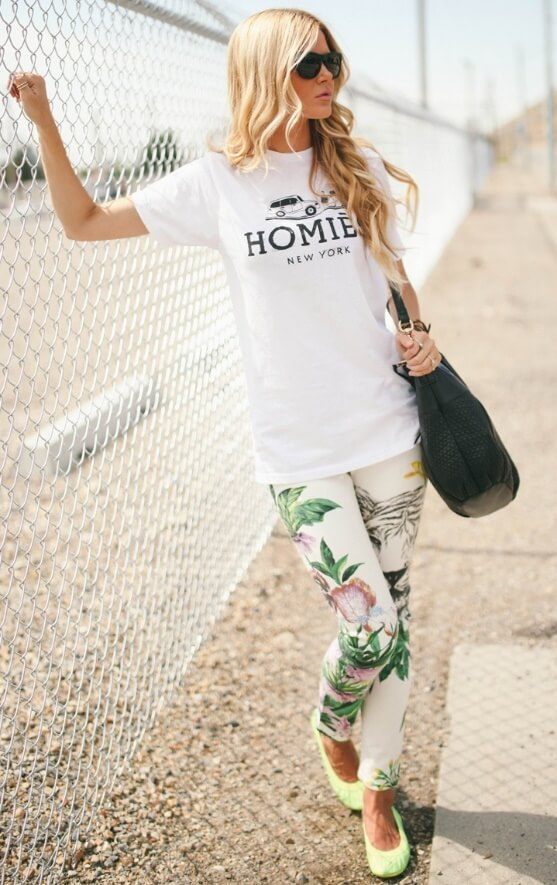 Stylish blonde wearing a white statement T-shirt and floral pants. Basic white plus tropical leafy florals make one mean team.