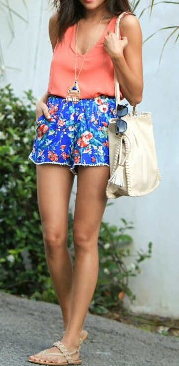 Stylish brunette is wearing floral shorts and a coral vest. It's time to pull out those floral shorts from last season. And if they have a tasseled hem, even better!