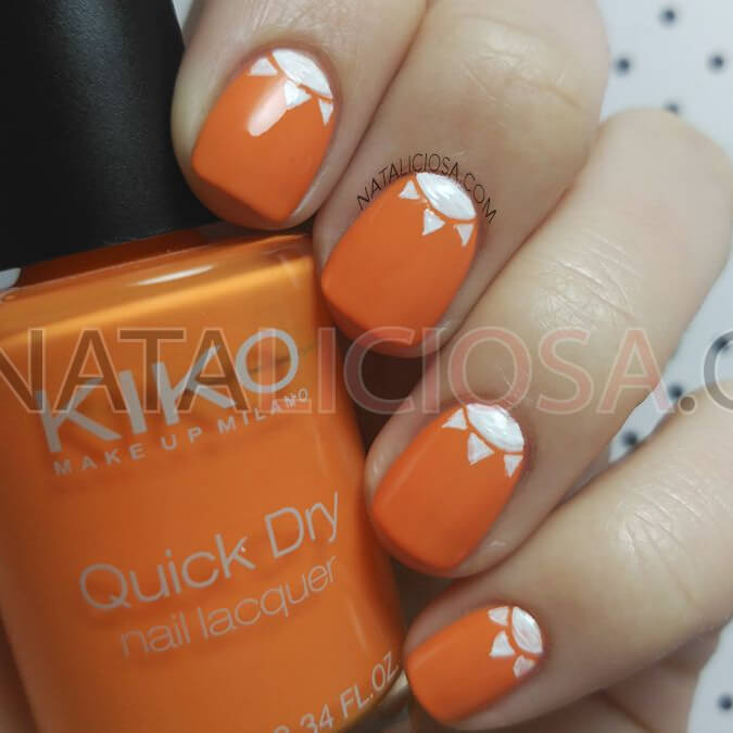 What better way to celebrate spring's arrival than to decorate your nails with this orange and white manicure, using a semi-circle and three triangles to create a small sun on each nail.