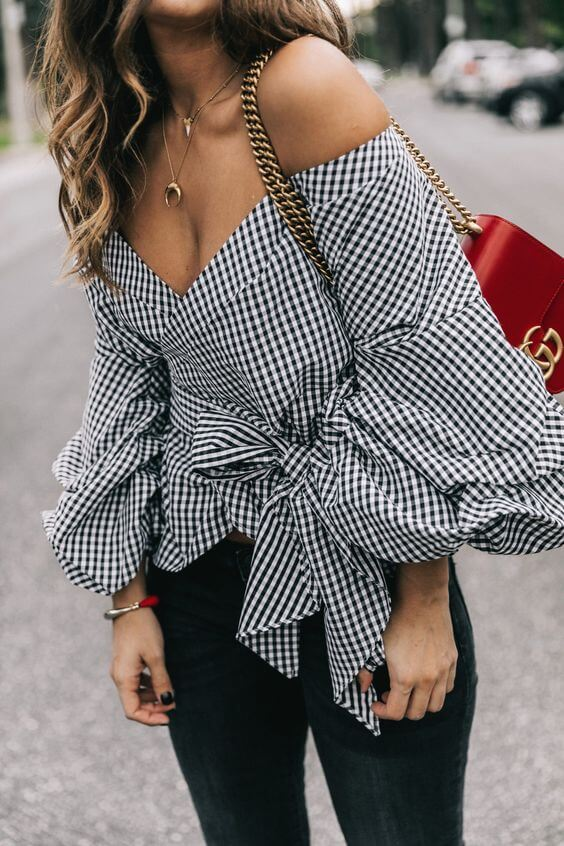 Trendy brunette is wearing distressed jeans and a gingham bell sleeve blouse. Add some fun and frivolity to blue jeans with a billowing gingham-print bell sleeve blouse.